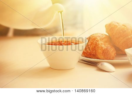 Cup of tea with croissants on table