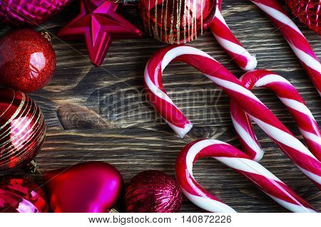 Christmas balls and candy canes on a wooden background.