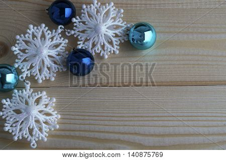 Snowflakes border and Christmas balls on wooden background. Christmas and New Year decoration