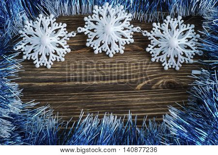 Snowflakes border on wooden background flat lay. Winter holidays concept.