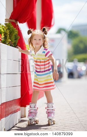 Cute little red-haired girl with hair in two ponytails,grey eyes and sweet smile,dressed in a multicolored striped dress with short sleeves,learning to roller skate in the city in the fresh air in the summer