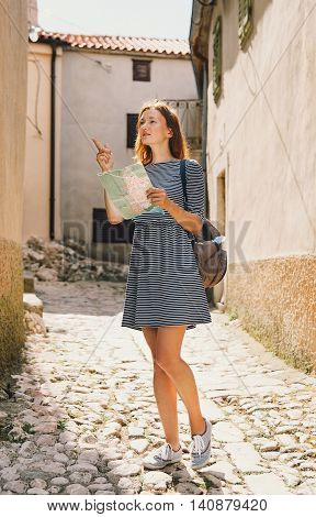 Young woman with a map indicating the side on the background of the old European streets. Krk Island Croatia