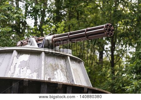 An old minigun on a stand in a forest.