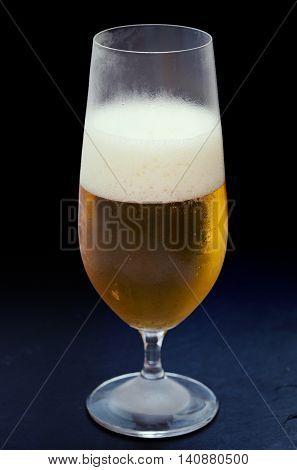 freshly poured glass of beer on black slate trivet