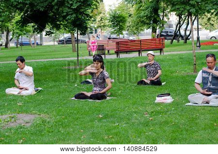 KHARKIV UKRAINE - JUNE 18 2016: People are practicing Falun Gong (Falun Dafa) - Chinese spiritual practice - in the central park of Kharkiv Ukraine