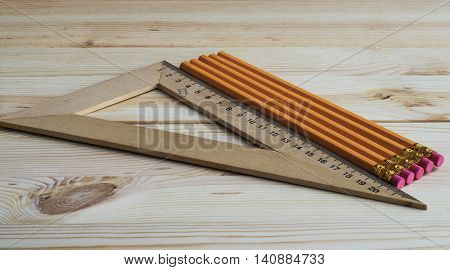 Triangle and pencils on the wooden background