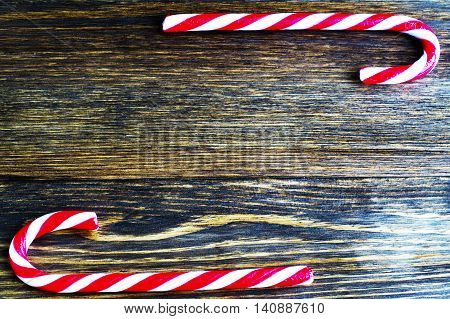 Christmas Candy on wooden background. Christmas balls and candy canes on a wooden background, flat lay
