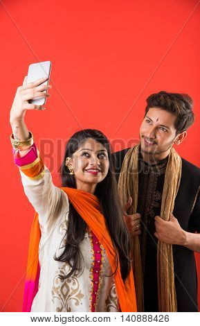 Indian brother taking selfie with sister on Raksha Bandhan festival after tying knot or rakhi