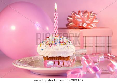 Little cupcake with candle, balloon and gift on pink background
