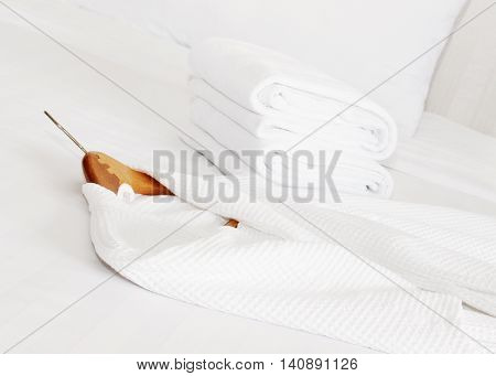 white bathrobe and towels on the bed