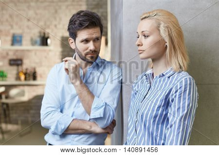 Young couple standing by wall at home, woman looking serious and hurt. Relationship difficulties.