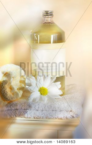 Bottle of linen water with towels and flower on cabinet