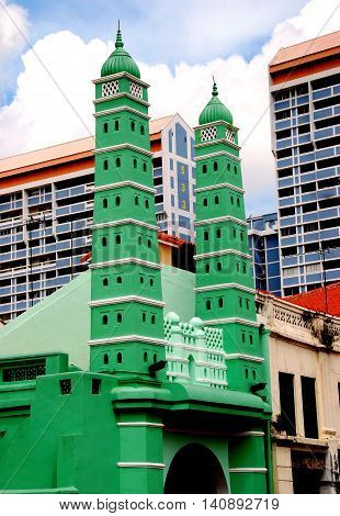 Singapore - December 14 2007: Twin minarets flank the street facade of the 1826 Jamae Chulia Mosque on South Bridge Road in Chinatown