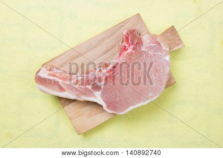 Raw porkchop on wooden broad / cooking porkchop steak concept