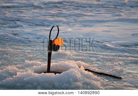 Fishing rod for winter fishing in the ice hole on the lake at sunset