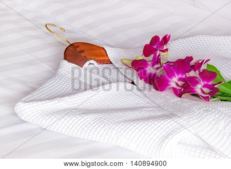 white bathrobe and orchids on the bed