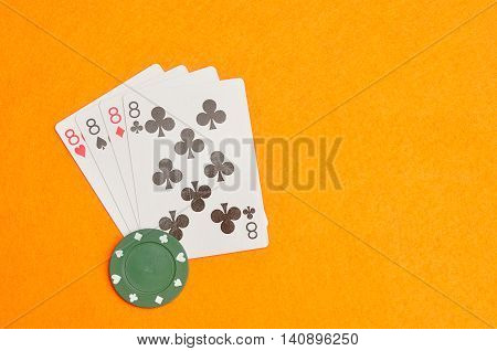 The different suit of the number 8 cards in a deck of cards displayed on an orange background displayed with a green poker chip