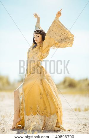 Fashion stylish beauty woman with black short haircut and professional make-up of Cleopatra. Girl standing in full lenght in golden dress outdoors in desert