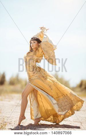 Fashion gorgeous beauty woman with black short haircut and professional make-up of Cleopatra. Girl standing in full lenght in golden dress outdoors in desert. Hot sunny windy weather