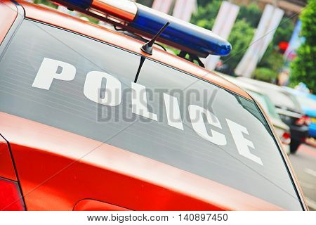 Closeup of the orange police car with a sign POLICE.