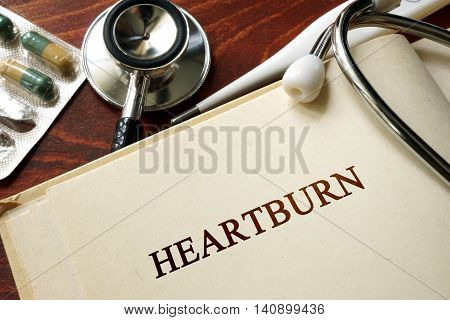 Page with word heartburn and glasses. Medical concept.