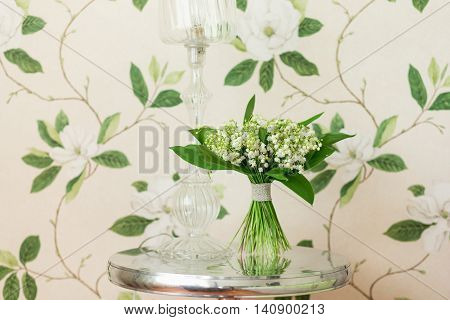 Small bouquet of Lily of the valley flowers standing on decorative metallic table with sea shells elements. Flower decor idea. Flower design. Interior