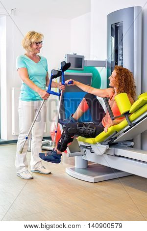 Physiotherapist helping patient retrieve crutches after performing rehabilitation exercises on weight machine