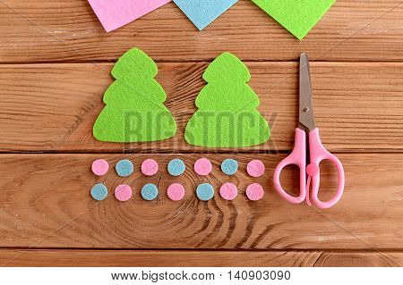 Green felt Christmas tree patterns, pink and blue balls, scissors on wooden background. How to make simple Christmas tree ornament. Master class for kids. Step