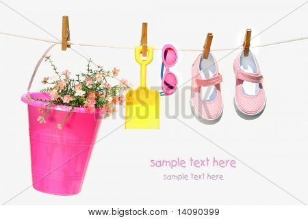 Pail,sunglasses and shoes for child on clothesline
