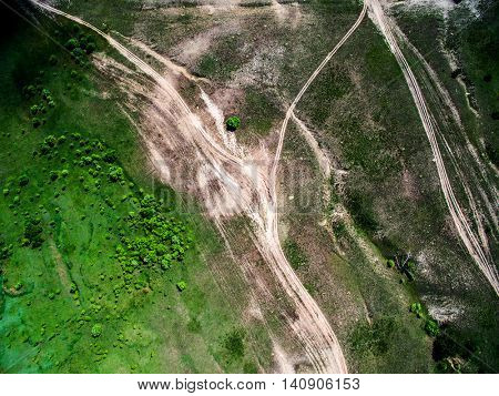 aerial photo of green field with trees and rolled roads, top view