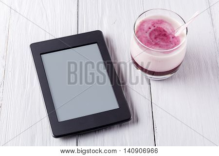 Berry smoothie with yogurt and eBook. Closeup