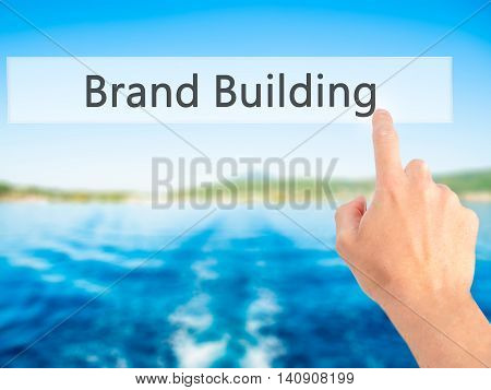Brand Building - Hand Pressing A Button On Blurred Background Concept On Visual Screen.
