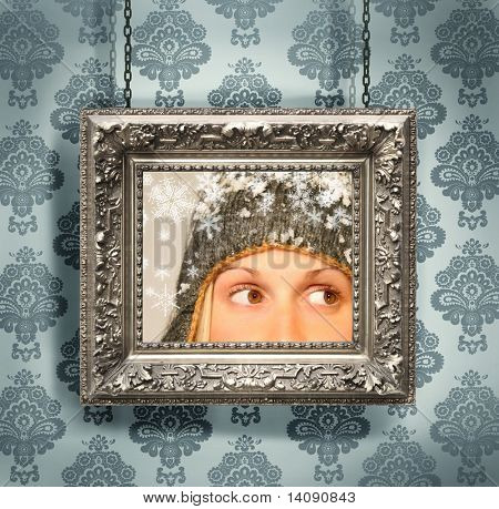 Silver picture frame hung against floral wallpaper background/ blue