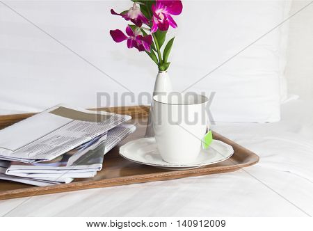breakfast , flowers and newspaper on the bed