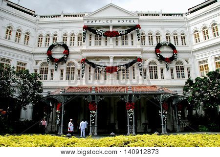 Singapore - December 16 2007: Grand facade of famed 1887 Raffles Hotel with Christmas wreaths and bunting decorations