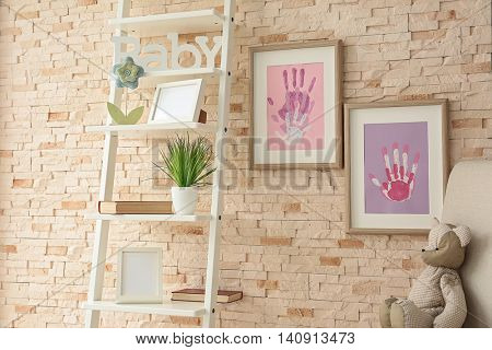 Family hand prints in frame hanging on brick wall