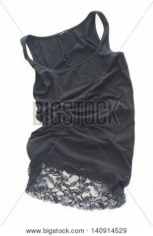 Black crumpled dress with guipure on a white background.