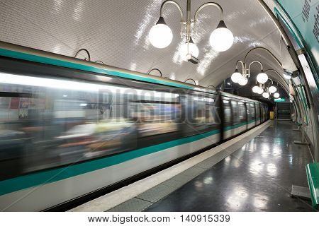 PARIS - JUNE 19 2015: A metro train leaving a Paris Metro station. Paris Metro is the 2nd largest underground system worldwide by number of stations (300).
