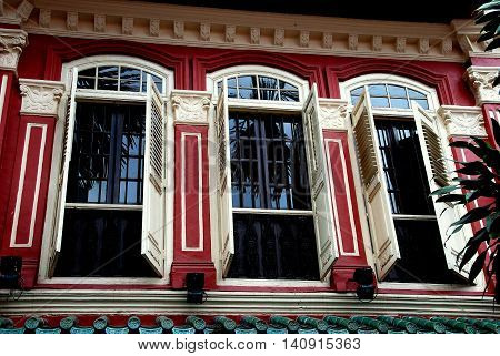 Singapore - December 15, 2007: Finely restored Peranakan home with large windows and louvered wooden shutters in the Emerald Hill Conservation Area
