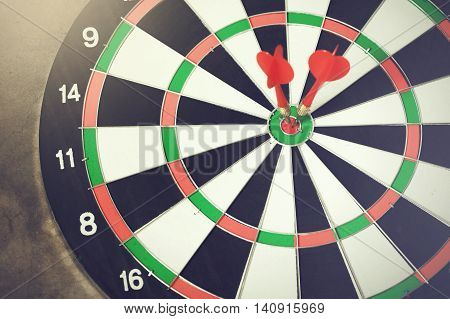 Darts accurately and perfectly hit the winning red spot on board (Focus on tip of the dart) - indicates right targeting marketing focus concept.