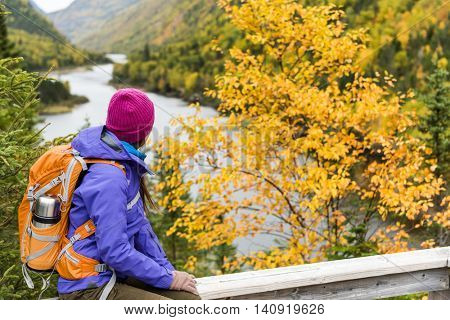 Woman hiker hiking looking at scenic view of fall foliage mountain river landscape . Adventure travel outdoors person standing relaxing at viewpoint during nature hike in autumn season.