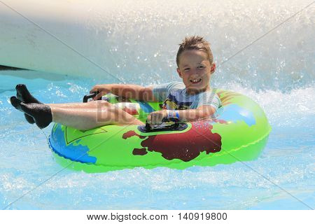 Rhodes Greece-July 31 2016:The boy joying after rafting slide in the Water park.Rafting slide is one of many popular game for adults and children in park. Water Park is located on the island of Rhodes in Greece and one of the most largest in Europe