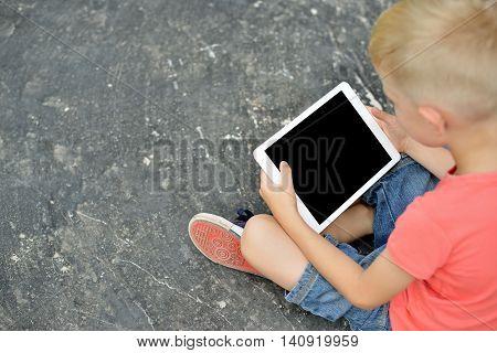 Teenage Boy Using A Digital Tablet In The Street