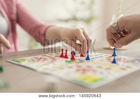 Close up of a couple in love sitting on the floor next to a table playing ludo board game and enjoying their free time together. Focus on the red figurine
