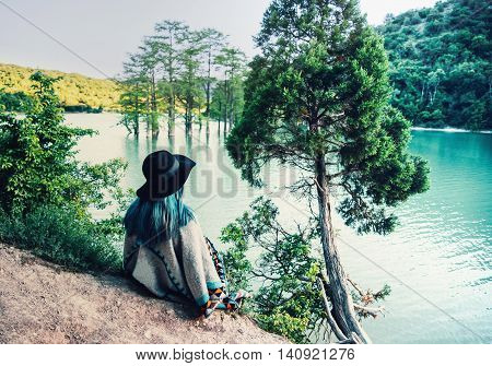 Young woman in hat and poncho resting on the shore of lake and enjoying view of nature