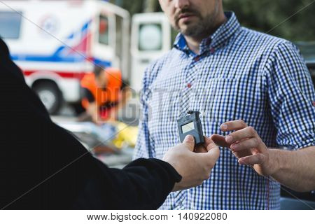 Police officer giving the breathalyser to the other man