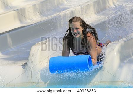Rhodes Greece-July 31 2016:Girl on the mat racer slide.Mat racer slide is very popular for young people in the Water Park.Water Park is located on the island of Rhodes in Greece and one of the most largest in Europe and is a very popular place