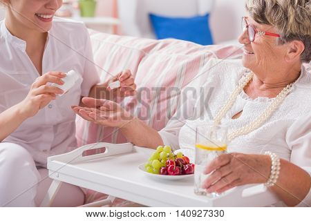 Smiled nurse preparing the dose of daily pills to senior patient