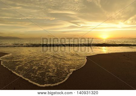 Ocean sunset is a brightly beach with the sun setting on the ocean horizon as a gentle wave rolls along the sandy shoreline.