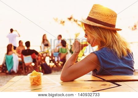 Young woman drinking beer in a beach bar